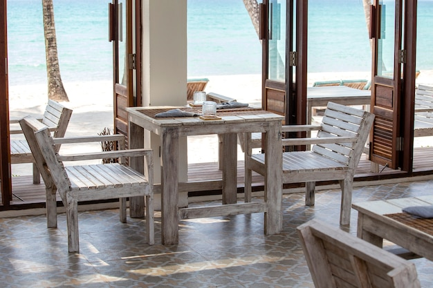 Tropical beach cafe with wooden table and chairs near the sea