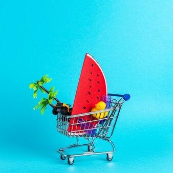 青い背景のショッピングトロリーで夏のもので作られた熱帯のビーチのコンセプト。