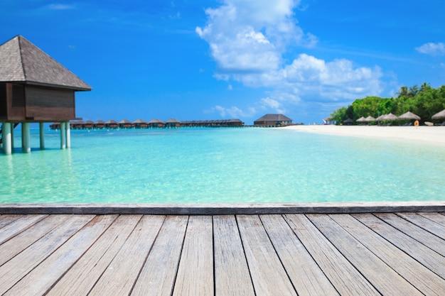 Тропический пляж на мальдивах с несколькими пальмами и голубой лагуной