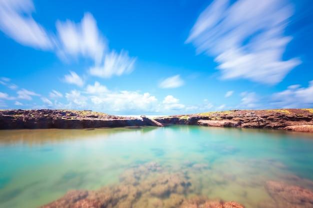 코코넛 나무와 바위 긴 노출 열 대 해변 풍경.