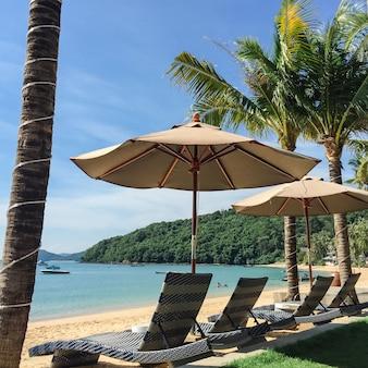Paesaggio tropicale della spiaggia con sdraio e ombrellone, da nosy be, madagascar - filtro leggero dell'annata.