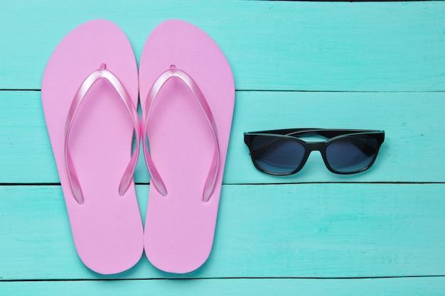 熱帯のビーチのライフスタイル。青い木製の背景にビーチサンダルとサングラス。夏の背景。上面図