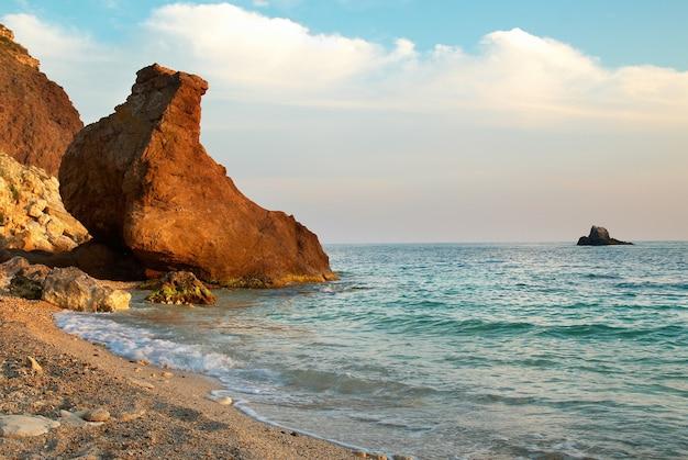 水と岩と夕日の熱帯のビーチ。
