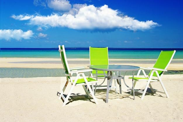 カフェテーブルとビーチの椅子のある熱帯のビーチの風景
