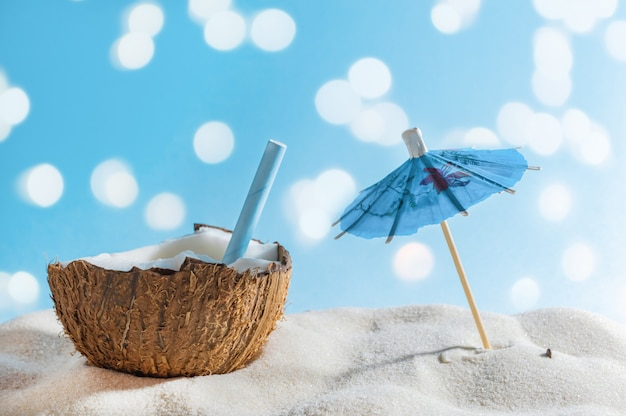 Tropical beach or travel concept: summer cocktail in coconut and sun umbrella.
