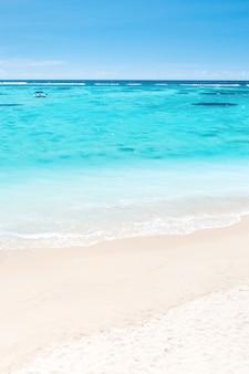 열 대 황금 모래 해변에 침입 하는 파도의 조감도와 열 대 해변. 아름다운 모래사장을 따라 바다의 파도가 부드럽게 휘어집니다.
