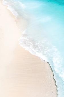 열 대 황금 모래 해변에 침입하는 파도의 조감도 볼 수있는 열 대 해변. 바다 파도가 아름다운 모래 해변을 따라 부드럽게 순환합니다.