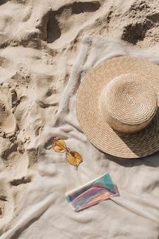 白い砂浜、足音、麦わら帽子、サングラス、ケースが付いたニュートラルな毛布のある熱帯の美しいビーチ