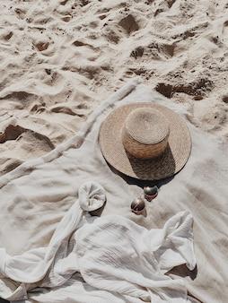 白い砂浜、足音、麦わら帽子、サングラス、白いシャツとニュートラルな毛布のある熱帯の美しいビーチ