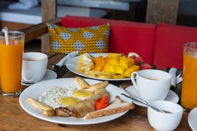 Тропический завтрак из фруктов, кофе, омлета и бананового блина на двоих на пляже у моря в ресторане отеля, остров занзибар, танзания, африка, крупным планом