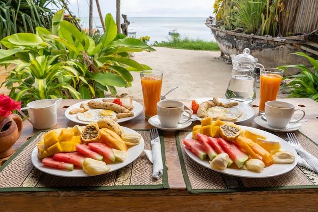 フルーツ、コーヒー、スクランブルエッグ、バナナのパンケーキのトロピカルブレックファースト