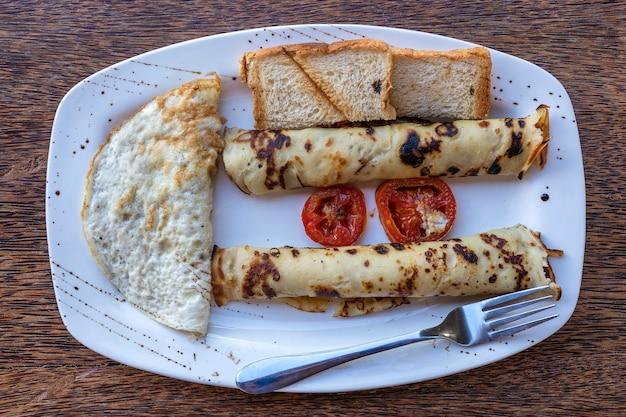 Тропический завтрак из яичницы-болтуньи и обернутых банановых блинов в ресторане отеля, остров занзибар, танзания, африка, крупным планом. вид сверху