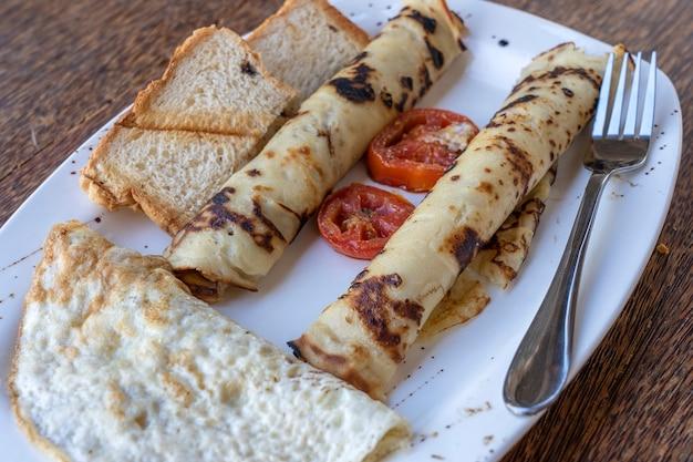 Тропический завтрак из омлета и обернутых банановых блинов в ресторане отеля, остров занзибар, танзания, африка, крупным планом