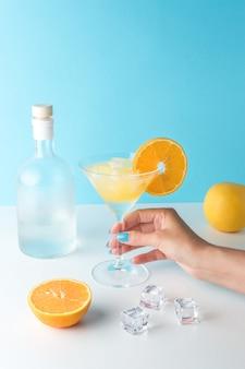 白いテーブルの上に角氷とアルコールのボトルとマティーニグラスのトロピカルカクテル