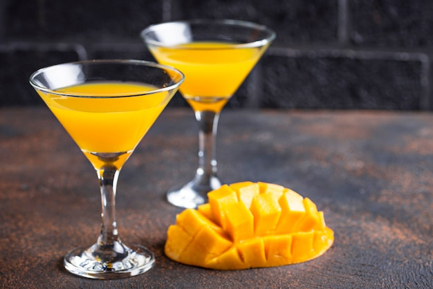 Tropical cocktail with mango on dark background