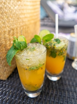 Tropical cocktail with passion fruit, lime and mint on the table near the pool