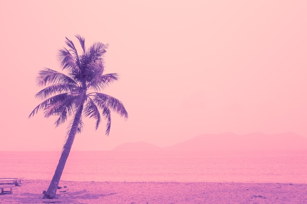 Tropical coconut tree against the background of the sea, bright purple and pink tint. travel and tourism. postcard, template for text.