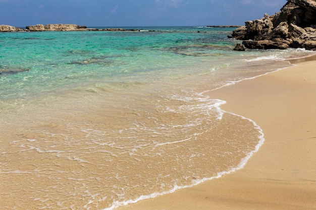Tropical cyprus paradise beach with white sand and stones, two beach bed in a corner, travel tourism wide panorama background concept