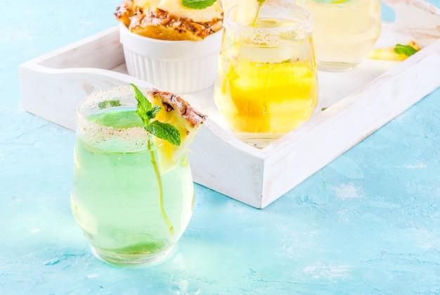 トロピカルドリンクパイナップルジュースマルガリータカクテル、新鮮なミントの明るい青の背景木製トレイ