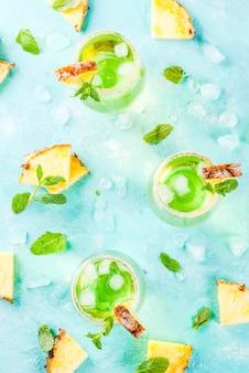 トロピカルドリンクパイナップルジュースマルガリータカクテル、新鮮なミントの明るい青の背景