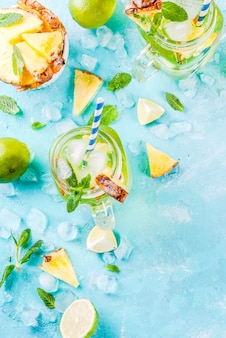 Tropical drink pineapple mojito or lemonade with fresh lime and mint light blue background