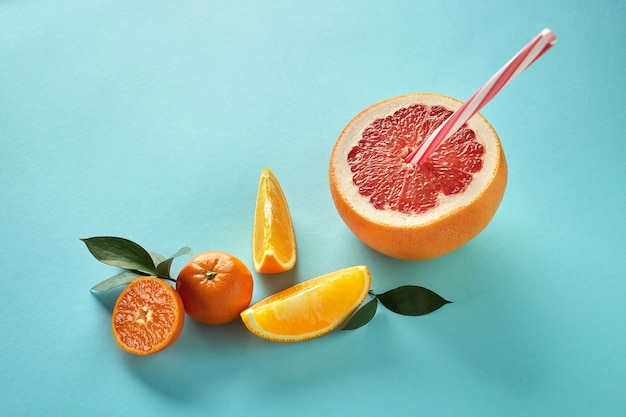 Tropical exotic citrus fruits half a grapefruit, tangerines, orange slices with a plastic straw for juice on a blue paper background