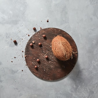 Tropical exotic fruit coconut with chocolate balls on a r wooden board on a gray stone table with place under text. top view. vegetarian concept of diet eating