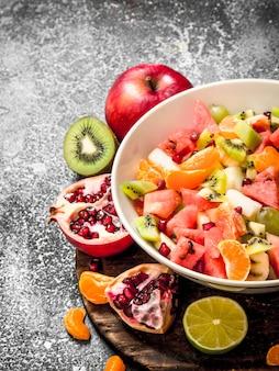 トロピカルフード素朴な背景にトロピカルフルーツサラダ