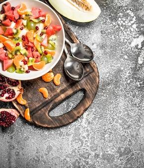 トロピカルフード。フルーツのフレッシュサラダ。素朴な背景に。