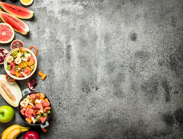 Tropical food . fresh tropical fruit salad in bowls. on rustic background.