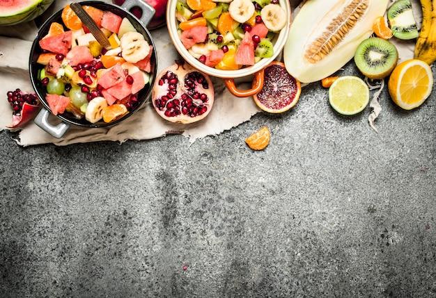 トロピカルフード素朴な背景のボウルに新鮮なトロピカルフルーツサラダ
