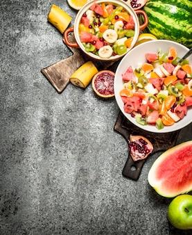 トロピカルフード。ボウルに新鮮なトロピカルフルーツサラダ。素朴な背景に。