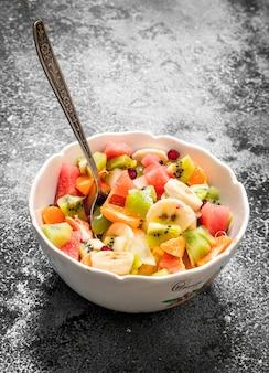 Тропическая еда фруктовый салат в миске на деревенском фоне