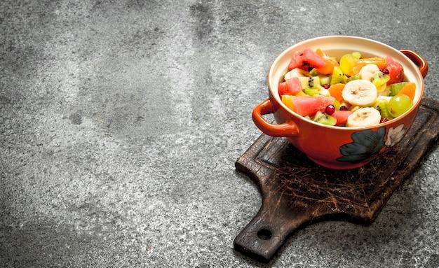 素朴な背景のボウルにトロピカルフードフルーツサラダ