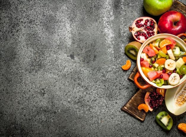 トロピカルフード。トロピカルフルーツサラダ。素朴な背景に。