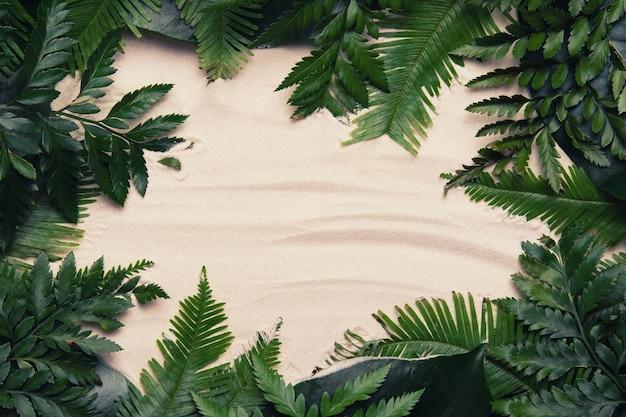 砂の背景にコピースペースとヤシの葉で作られたトロピカルフレーム。フラットレイ