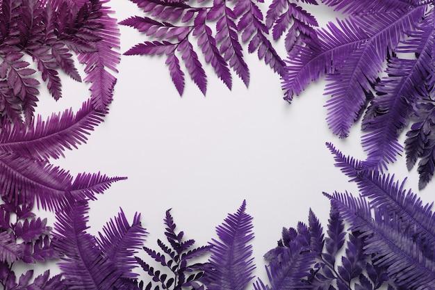 コピースペースの背景を持つヤシやシダの葉で作られたトロピカルフレーム。フラットレイ。