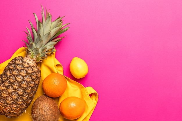 Tropical fresh exotic fruits with a yellow cotton bag on a yellow background. flat lay. food concept.