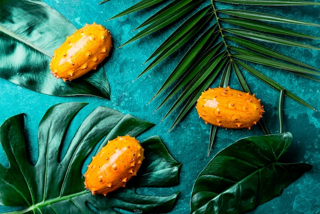 Tropical fruin kiwano passion fruit in green bowl on turquoise  with tropical palm tree leaves. top view. tropical