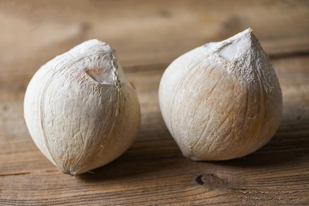 木製のテーブルにトロピカルフルーツココナッツ、食品用の新鮮なココナッツ