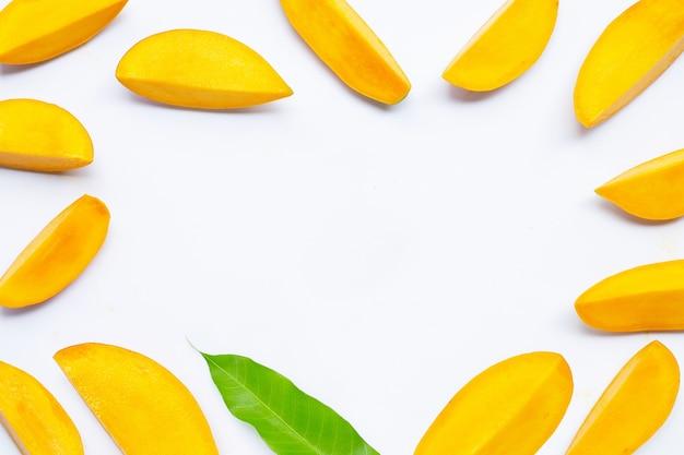 Тропические фрукты, рамка из ломтиков манго на белом фоне. вид сверху