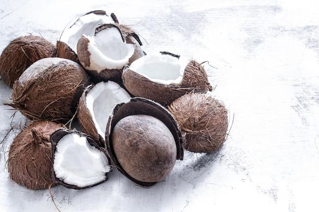 Тропический фрукт разрезанный вдвое розбитого кокоса на светлом фоне, концепция органических фруктов