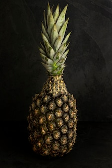 Tropical fruit: isolated pineapple, over black stone background.