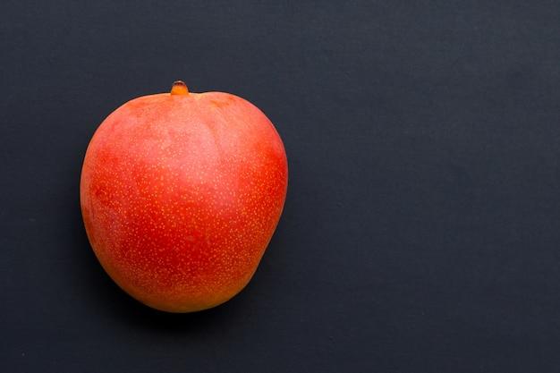 Tropical fruit, mango on dark background.