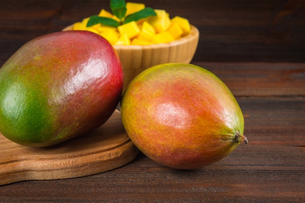Tropical fruit mango in a plate on a wooden background, whole or sliced.