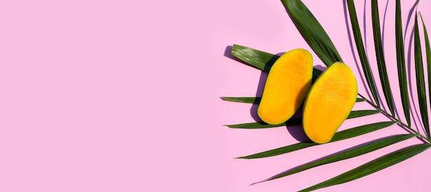 Tropical fruit, mango slices on pink background.