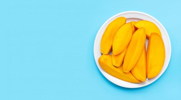 Tropical fruit, mango slices on white dish on blue background.
