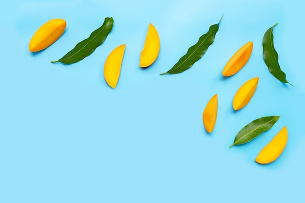 Tropical fruit, mango slices with leaves on blue background.