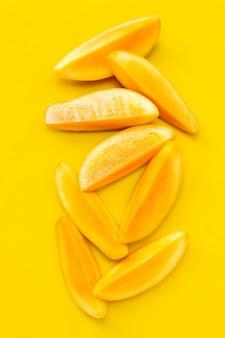 Tropical fruit, mango  slices on yellow. top view