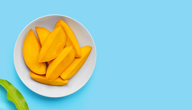 Tropical fruit, mango on white plate on blue background. top view